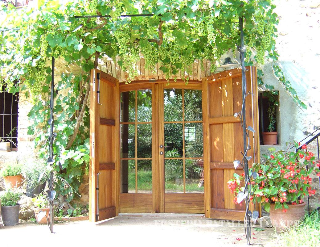 Porta exterior amb porticons i vidriera Iroko oberta