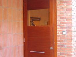 Porta exterior amb plafons i finestra Iroko