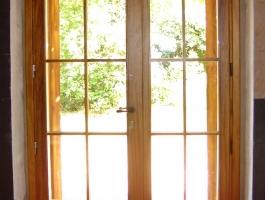 Porta exterior amb porticons i vidriera Iroko vista interior